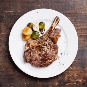 Ribeye Steak with vegetables on dark wooden background